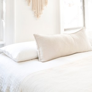 white sheets, white pillows, bright windows beside bed.