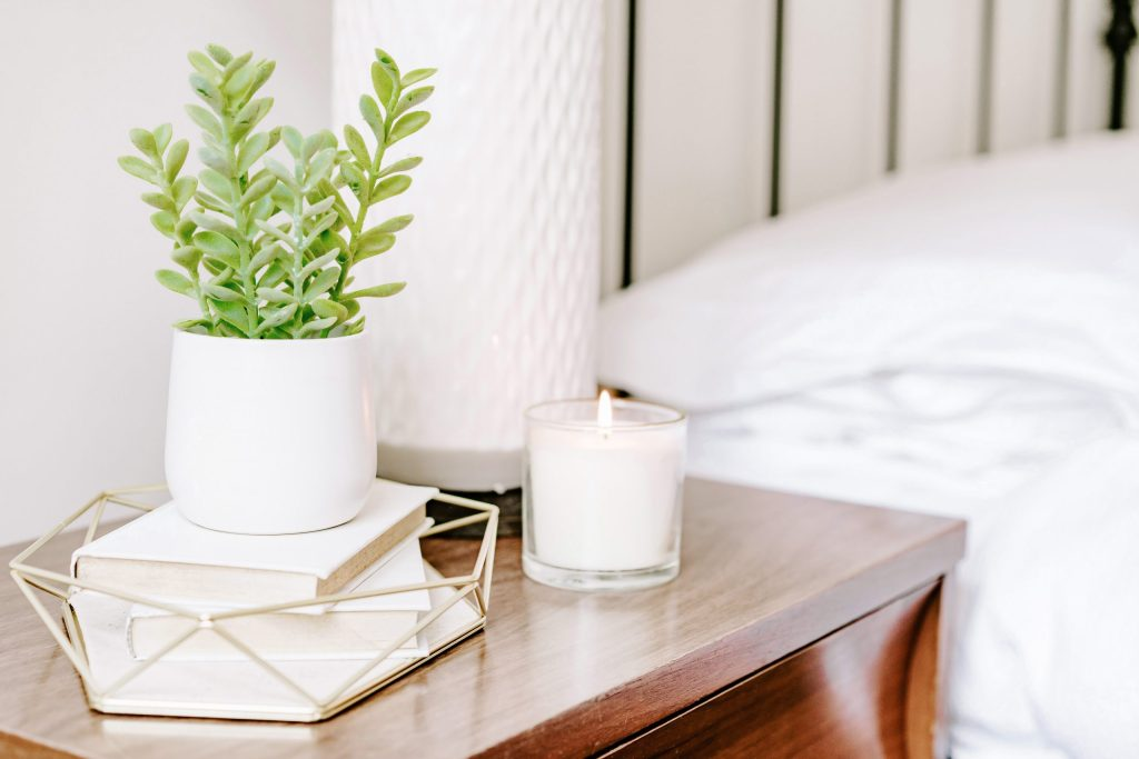 bedside table, plant, lit canlde, books, knick knacks. wooden table. 10 tips for the aspiring plant mom