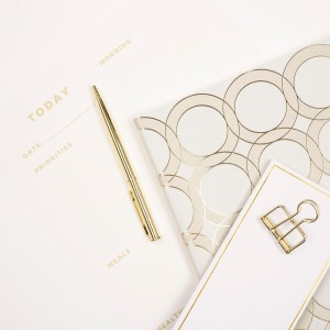 gold and white flatlay. papers, pens, binder clips, daily planner.