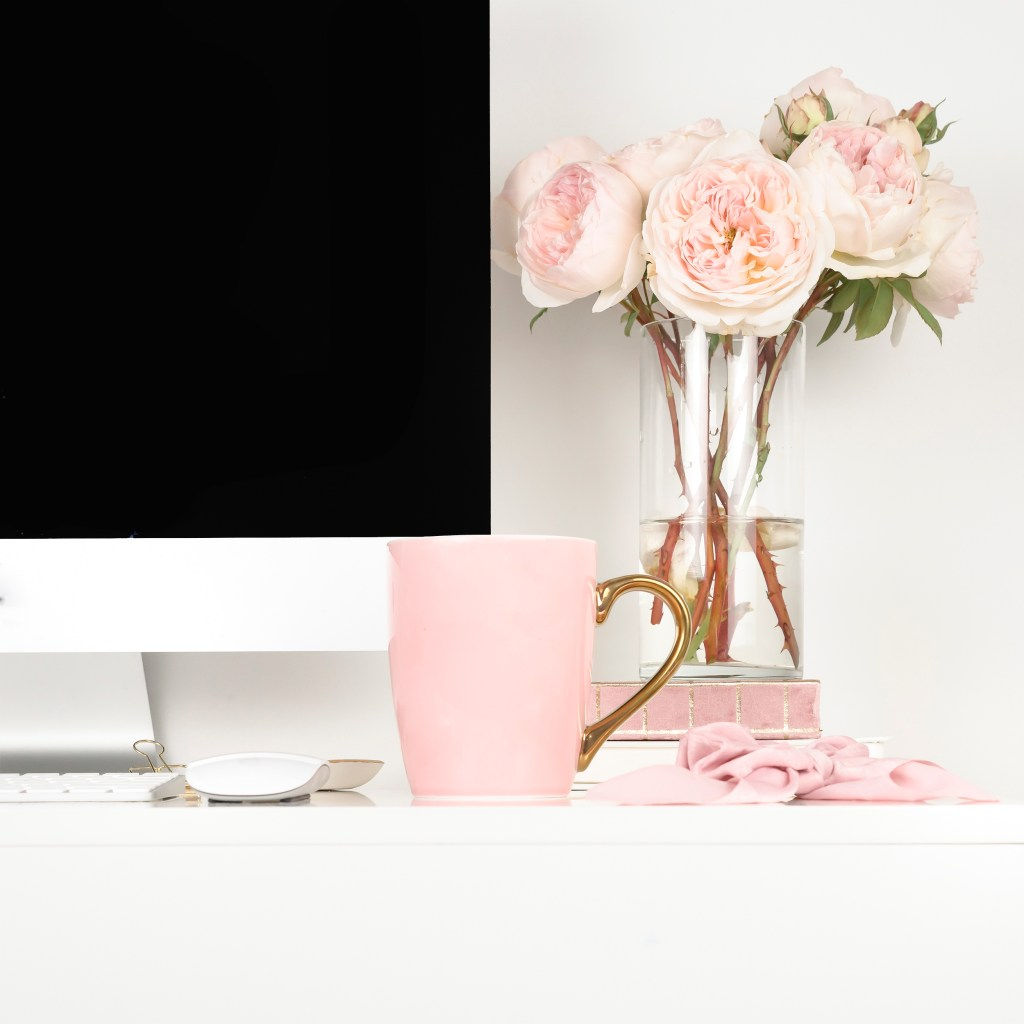 desk top apple computer, pink roses in vase, pink mug. how to network using twitter