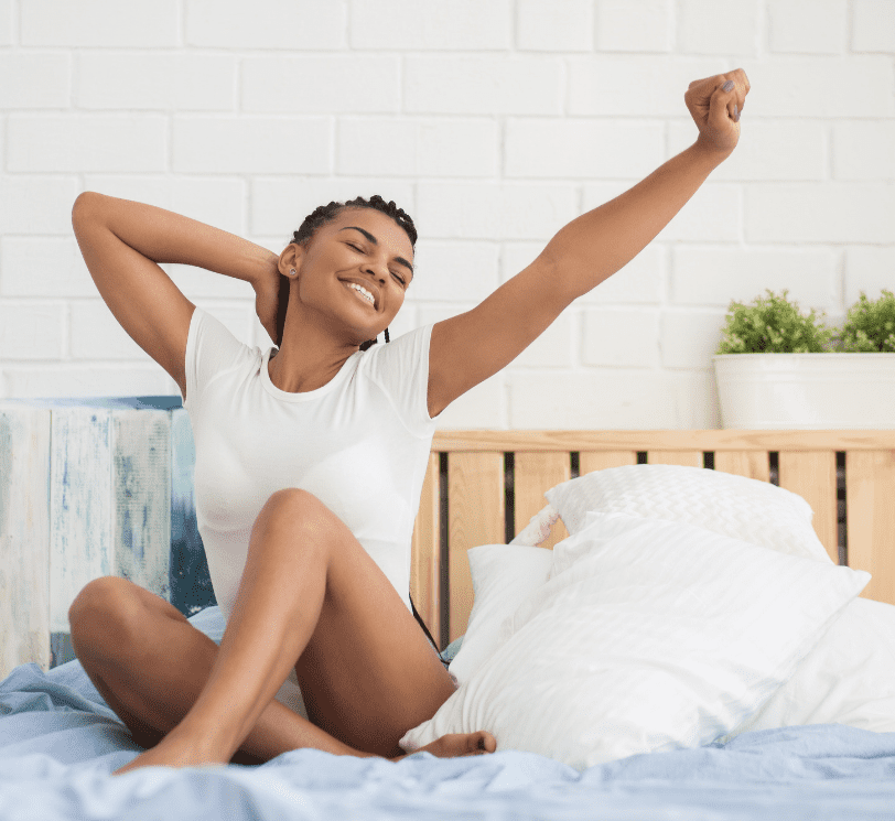 woman stretching sitting in her bed in the morning