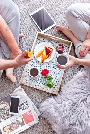 man and woman having breakfast date over tray on the floor. Ipad, iphone, fuzzy rug. Grey tones throughout.