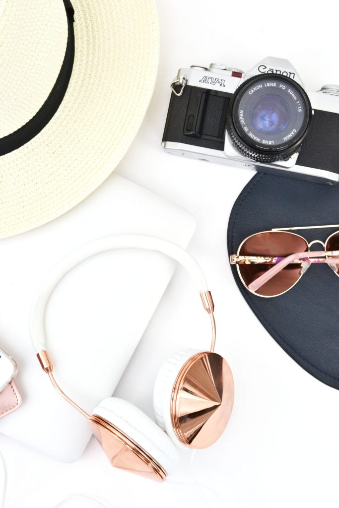 camera, sunglasses, headphones, hat, laptop flatlay. 100+ Summer Blog Content Ideas
