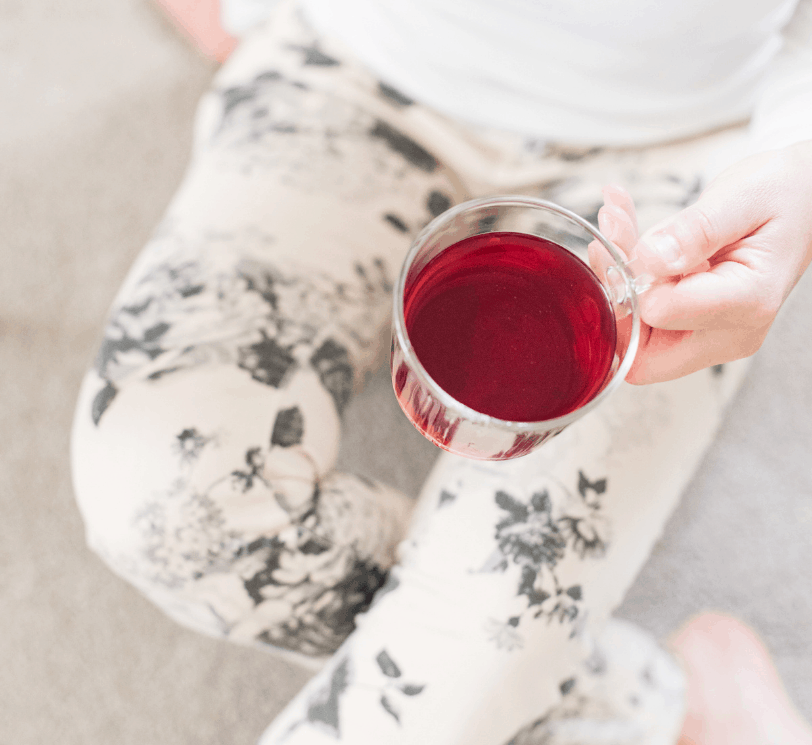 woman sitting with red herbal tea and patterned leggings