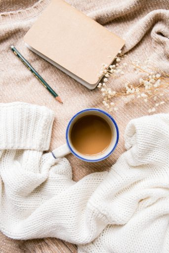 live a cozier life. brown and white sweater, coffee in white mug with blue rim, baby's breath, notebook and pencil.