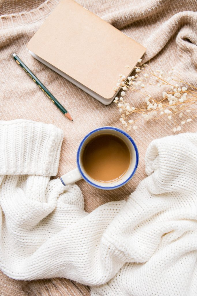 brown and white sweater, coffee in white mug with blue rim, baby's breath, notebook and pencil.