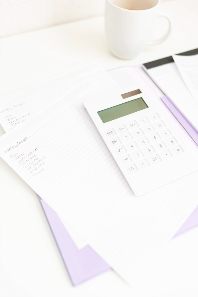 notebook, calculator, cup of coffee and lilac coloured folder. Crushing Your Debt - Why Sooner is Better Than Later