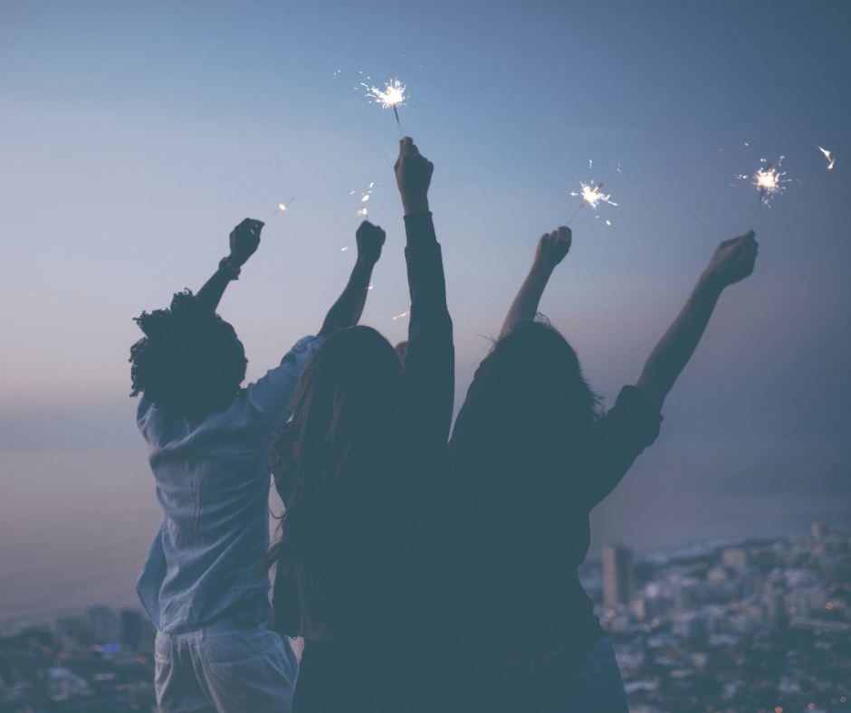 people holding sparklers in air, overlooking town.
