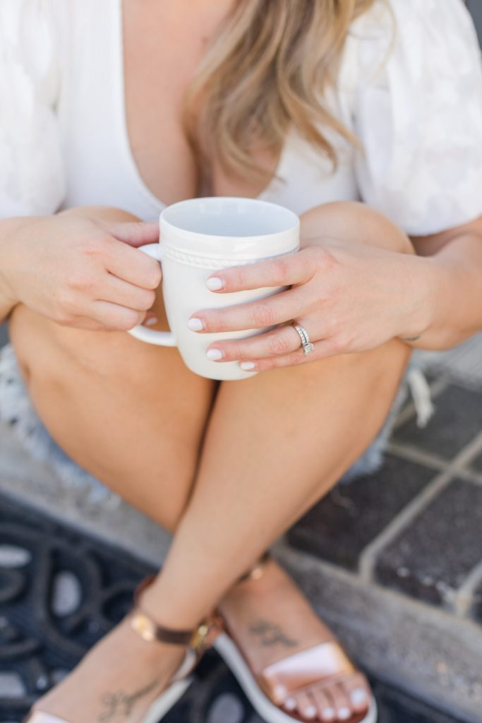 woman sitting with coffee cup on front step, sandals on.Putting Yourself First Isn't Selfish: How to Make Yourself a Priority