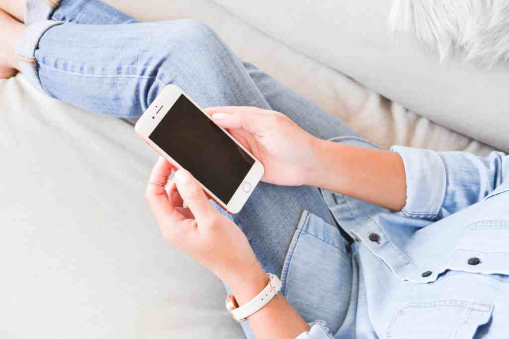 woman in blue shirt and jeans, sitting on the couch on her phone.