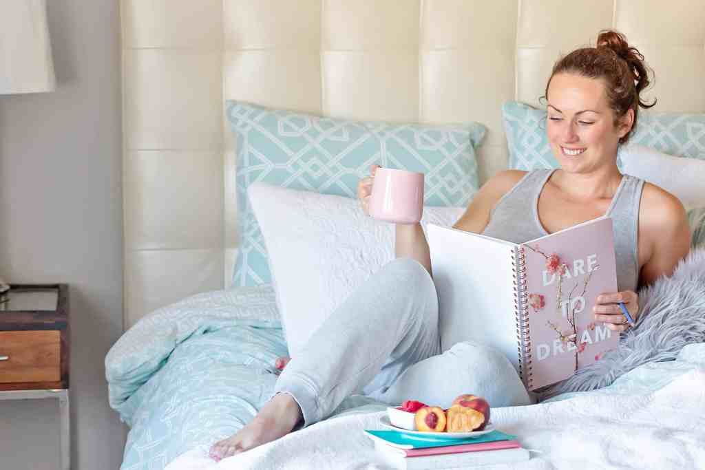 woman in bed with cup of coffee and food, notebook reads dare to dream. How to Live a More Intentional Life: 23 Ideas to Inspire You