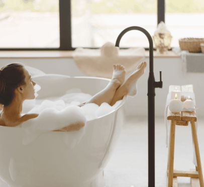 woman sitting in bathtub, candles lit around her. ACHIEVING WELLNESS: WHAT DOES THAT LOOK LIKE AND WHY IS IT DIFFERENT FOR EVERYONE?