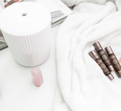 saje wellness diffuser, roller balls, chystal quartz, book, blanket. 11 SAJE WELLNESS MUST-HAVES YOU NEED IN YOUR LIFE