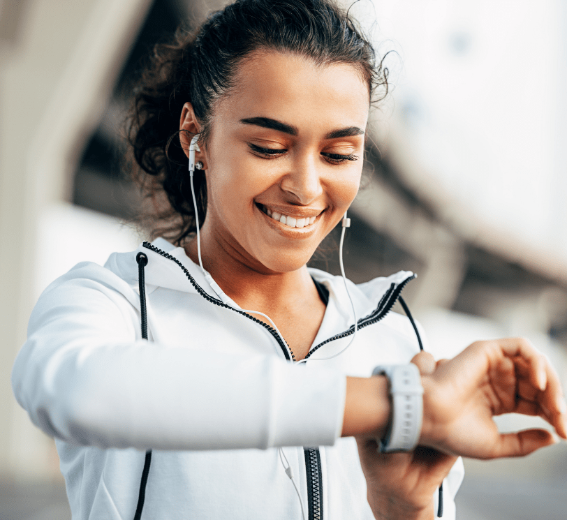 woman wearing workout attire and headphones looking at her fitness watch. 57 SIMPLE WAYS YOU CAN ENHANCE YOUR WELLNESS IN 2021: THE BODY & MIND EDITION