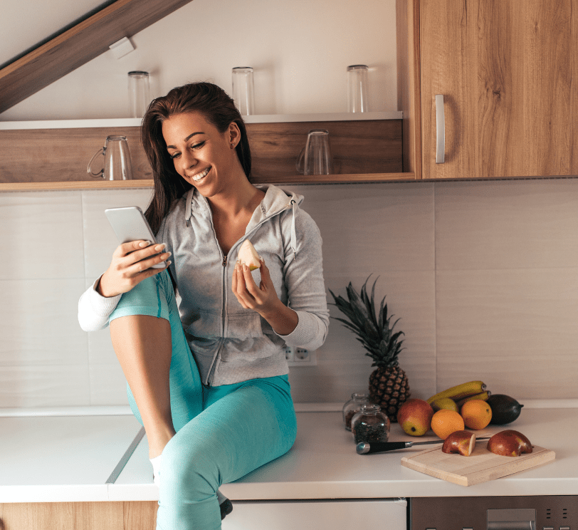 woman sitting on counter eating fruit on her phone