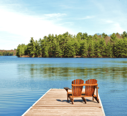 two wooden chairs at the end of the dock facing the lake