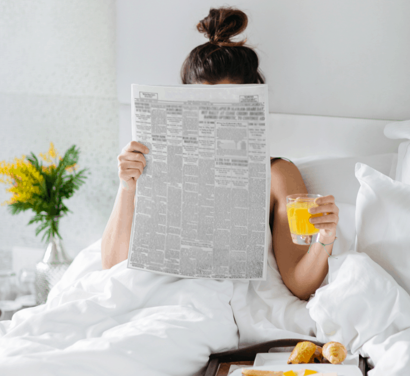 woman holding a glass of orange juice in bed, reading the paper. Hair up in a bun and flowers at the bedside.