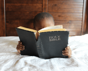A small child reading the Bible