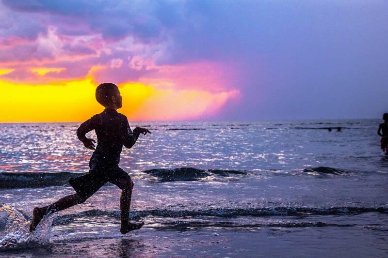 薄暗い砂浜の水際を走る子ども