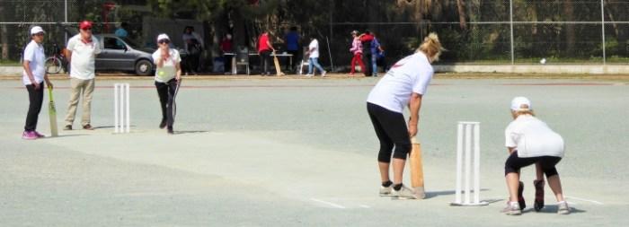 Katy Eliza bowling against the South Cyprus team, with wicket keeper Lynn Holman and umpire Nigel Holman