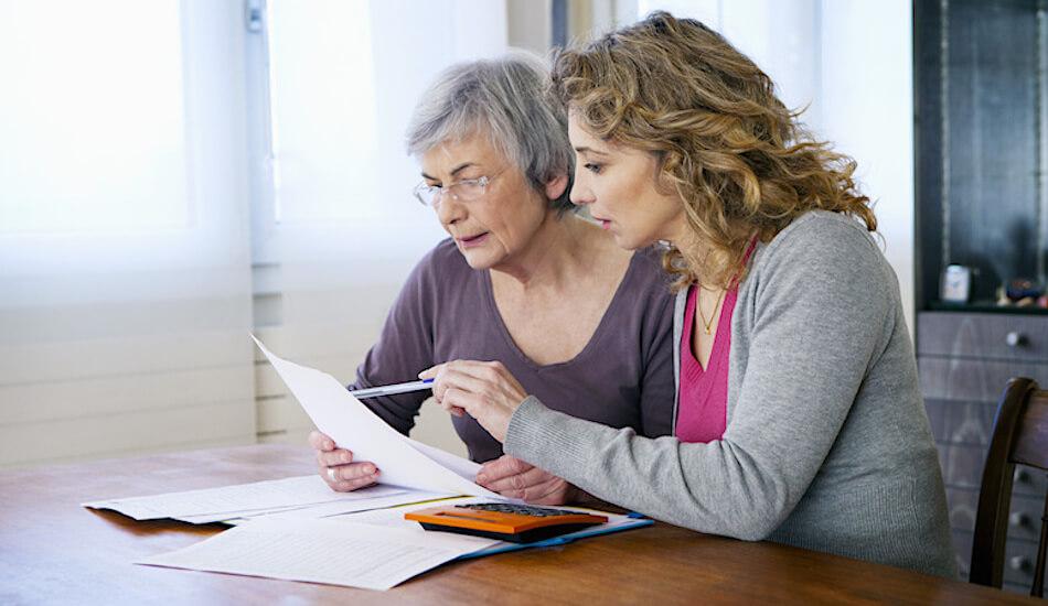 Starija i mlađa žena za uredskim stolom pregledavaju dokumente - fotografija