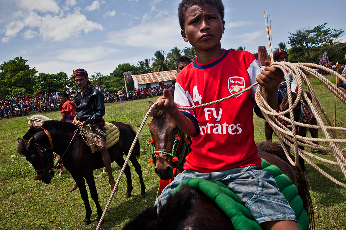 A boy wearing an Arsenal shirt sits on horseback at the festival