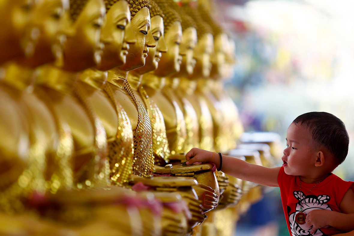 photo essay buddhists around the world celebrate vesak buddhist a child drops coins into golden buddha statues on vesak day at the thai buddhist chetawan