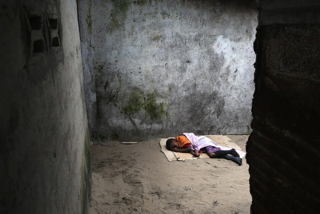 Ten-year-old Saah Exco lies in a back alley of the West Point slum in Monrovia, Liberia. The boy was one of the patients pulled out of a holding centre for suspected Ebola patients when the facility was overrun by a mob on Saturday. A local clinic refused to treat the boy, according to residents, because of the danger of infection