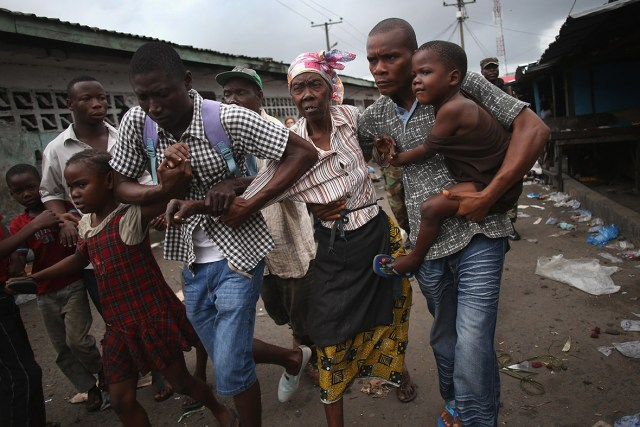 Family members of West Point district commissioner Miata Flowers flee the slum while being escorted by the Ebola Task Force