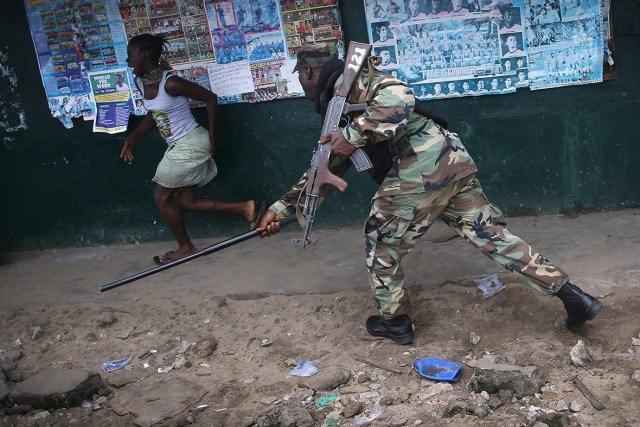 A Liberian Army soldier chases a resident while enforcing a quarantine on the West Point slum in an effort to contain the virus