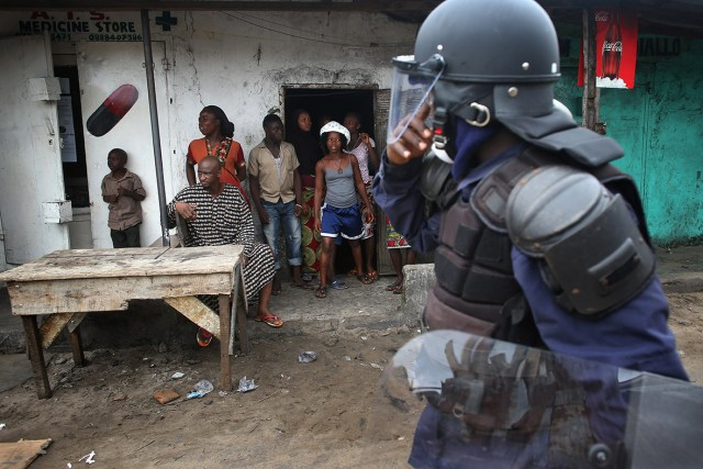 An Ebola Task Force officer walks into the West Point slum as the military began enforcing a quarantine on the congested favela of 75,000