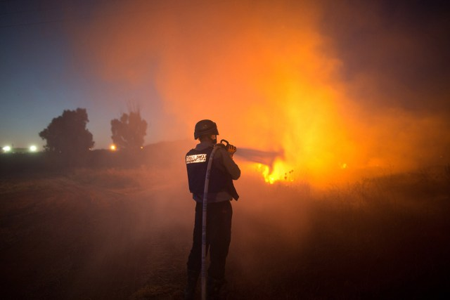 An Israeli firefighter extinguishes fire after rockets fired by Palestinian militants from the Gaza strip hit a field near the southern Israeli city of Sderot