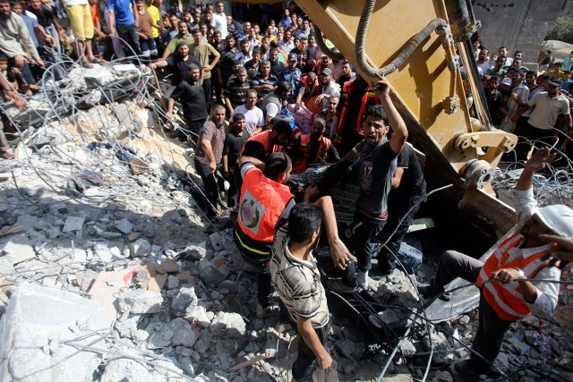 Palestinian rescue workers use an excavator to help remove the body of a man from under the rubble of a house in Rafah