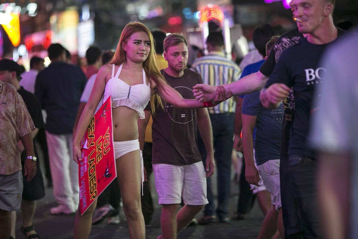 A Thai bar girl grabs men, trying to lure then into a bar in the red light district