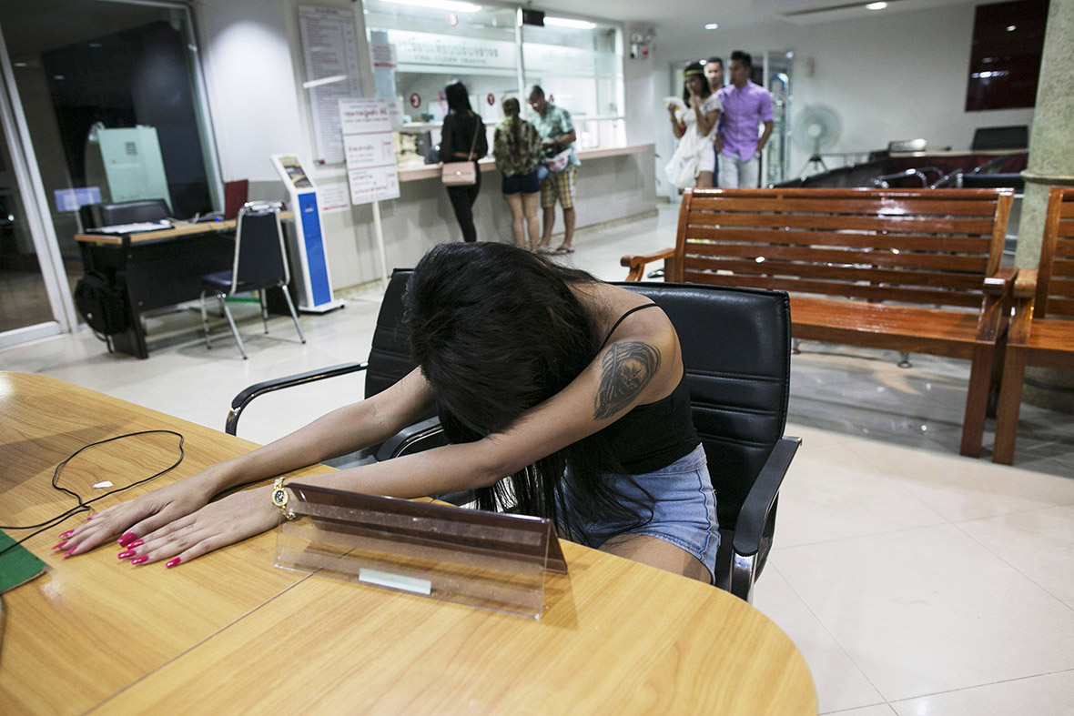 A Thai prostitute sits at the Pattaya police station after being arrested for allegedly stealing money and other personal items from a Chinese tourist