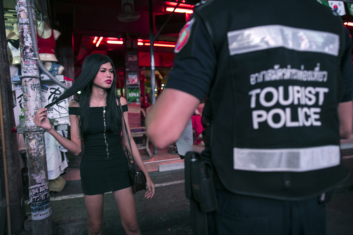 A member of the tourist police speaks to a suspected transsexual prostitute in the red light district