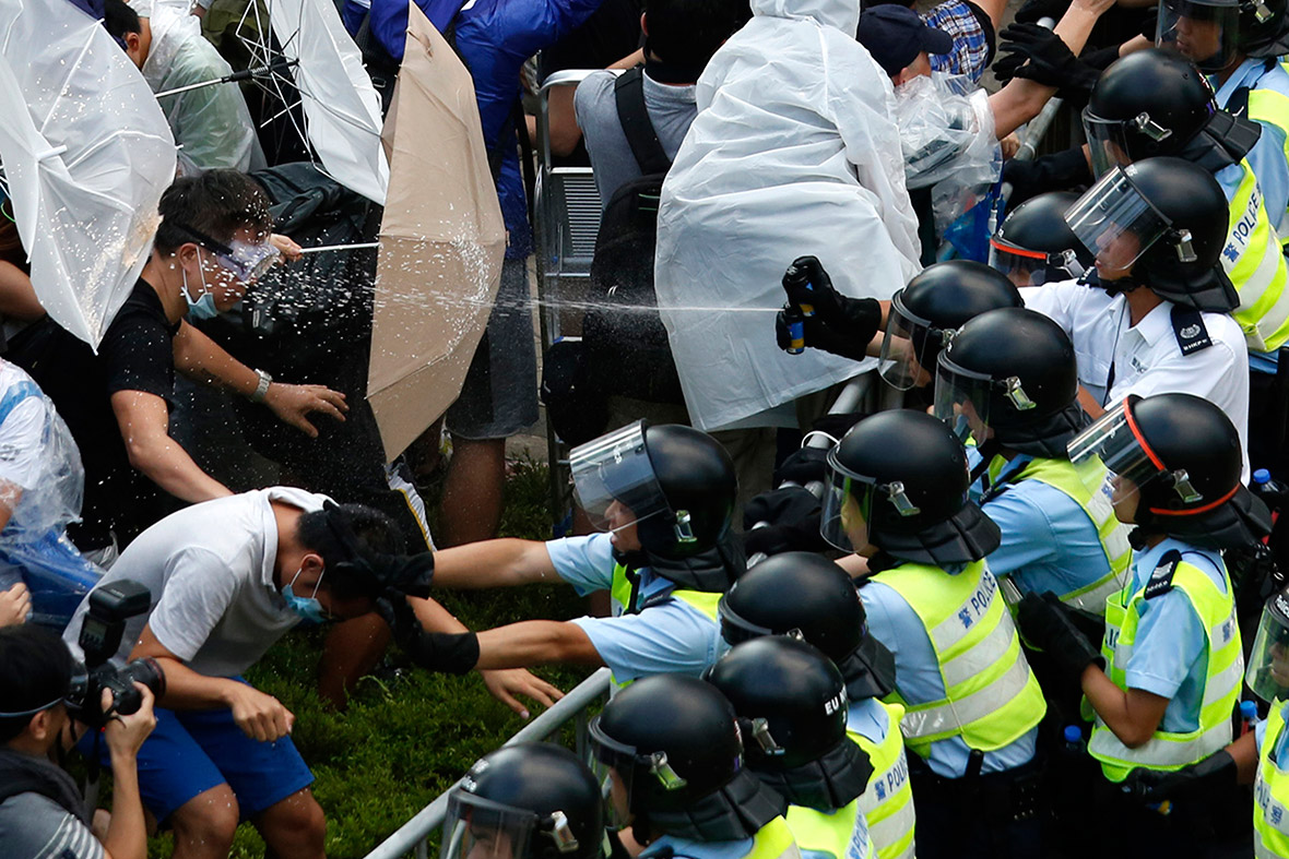 Riot police use pepper spray as they clash with protesters outside the government headquarters in Hong Kong