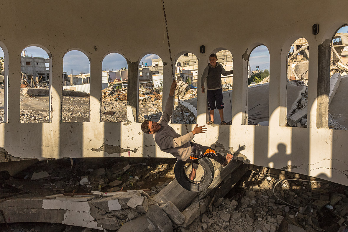 gaza strip blitzed caged and broken palestinians nightmarish children play in the ruins of a mosque s dome in khuzaa thousands of bombs rockets and other unexploded ordnance are thought to be buried in the rubble