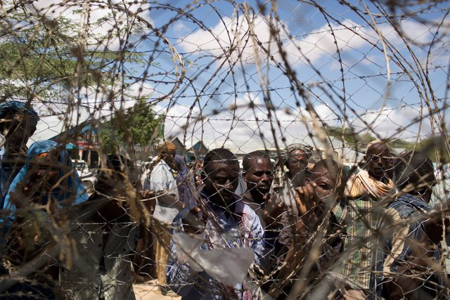 Somali refugees look through the barbwire fence of a United Nations World Food Programme (WFP) distribution centre during a food distribution exercise in Dagahale, one of several refugee settlements in Dadaab on 8 October 2013Siegfried Modola/Reuters