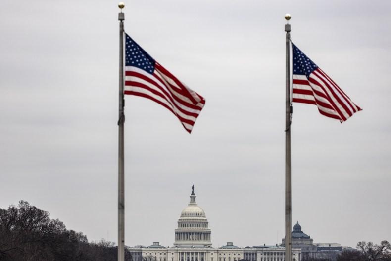 U.S. Capitol behind waving American flags