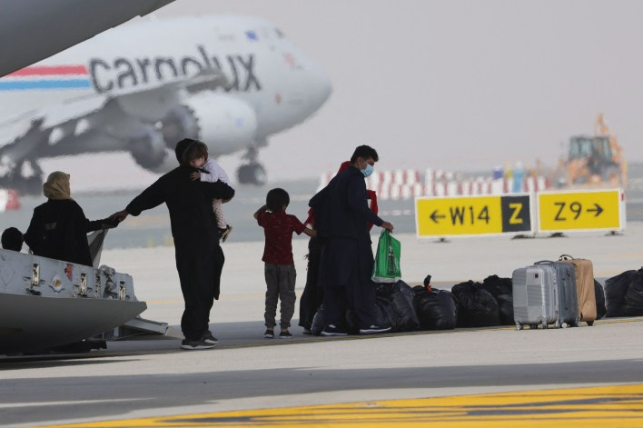 Evacuees from Afghanistan disembark a plane.