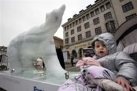 AP - A child is seen next to a melting ice statue of a polar bear in the center of ...