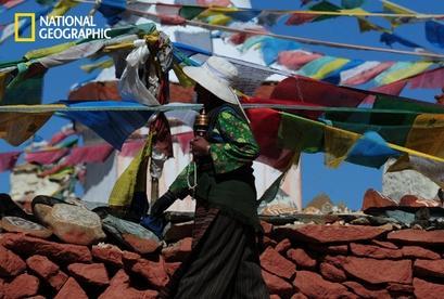 A Tibetan woman with her prayer wheel walking ...