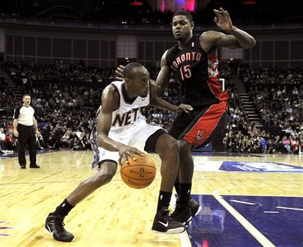 New Jersey Nets Travis Outlaw , left, takes the ball around Toronto Raptors Amir Johnson during their NBA basketball match at the O2 Arena in London, Saturday, March 5, 2011.