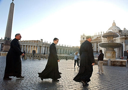 AP – Three priests cross St. Peter's Square at the Vatican, in this Oct. 18, 2002 file photo. (AP Photo/Luciano