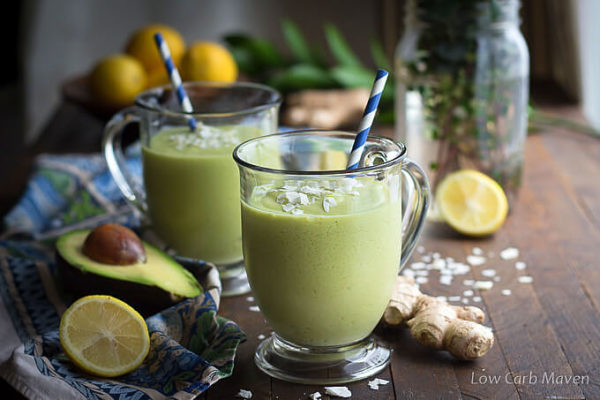 Two green avocado coconut smoothies in clear glass footed mugs with blue and white straws on a brown wooden board next to a blue napkin with cut avocado, lemons, ginger and coconut flakes.