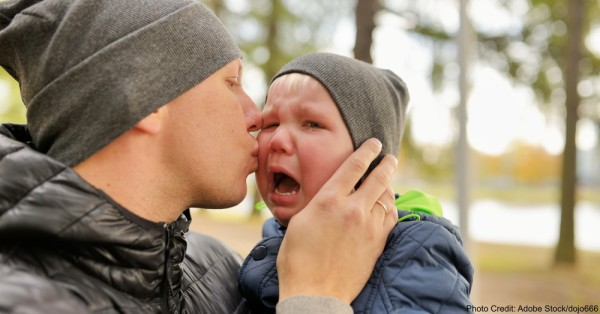 Father kiss crying child whom holds on hands