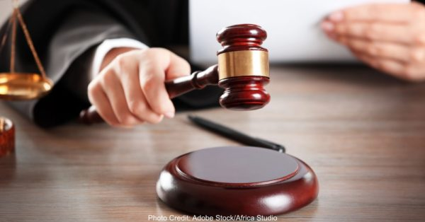 Judge hitting gavel with paper at wooden table closeup