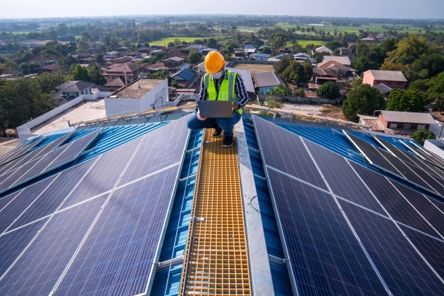 D1G Solar team member with laptop, crouching on a roof with solar panels, happy with his career.