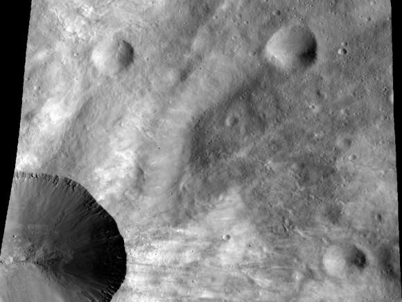 La imagen de la nave espacial Dawn de la NASA muestra un primer plano de una parte del borde alrededor del cráter Canuleia en el asteroide Vesta gigante.  Canuleia, cerca de 6 millas (10 kilómetros) de diámetro, es el gran cráter en la parte inferior izquierda de esta imagen.  Crédito de la imagen: NASA / JPL-Caltech / UCLA / MPS / DLR / ISP / Castaño